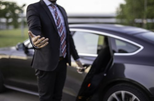 Handsome young man chauffeur holding a door and reaching out hand to help