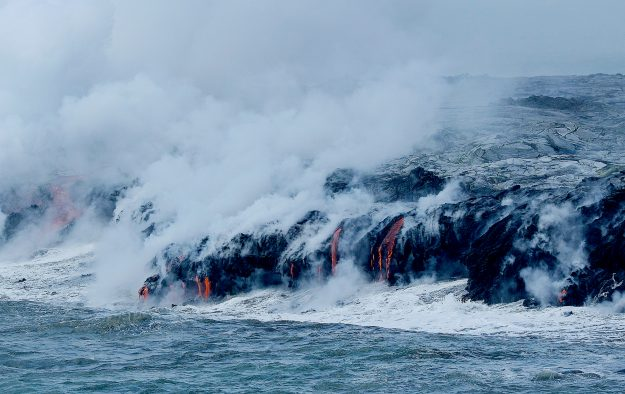 The lava flow of Kilauea volcano on the island of Hawaii flows into the ocean at Volcanoes National Park.