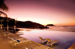 Dreams Huatulco Resort & Spa - Grounds - A view at dusk of the ocean front infinity pool