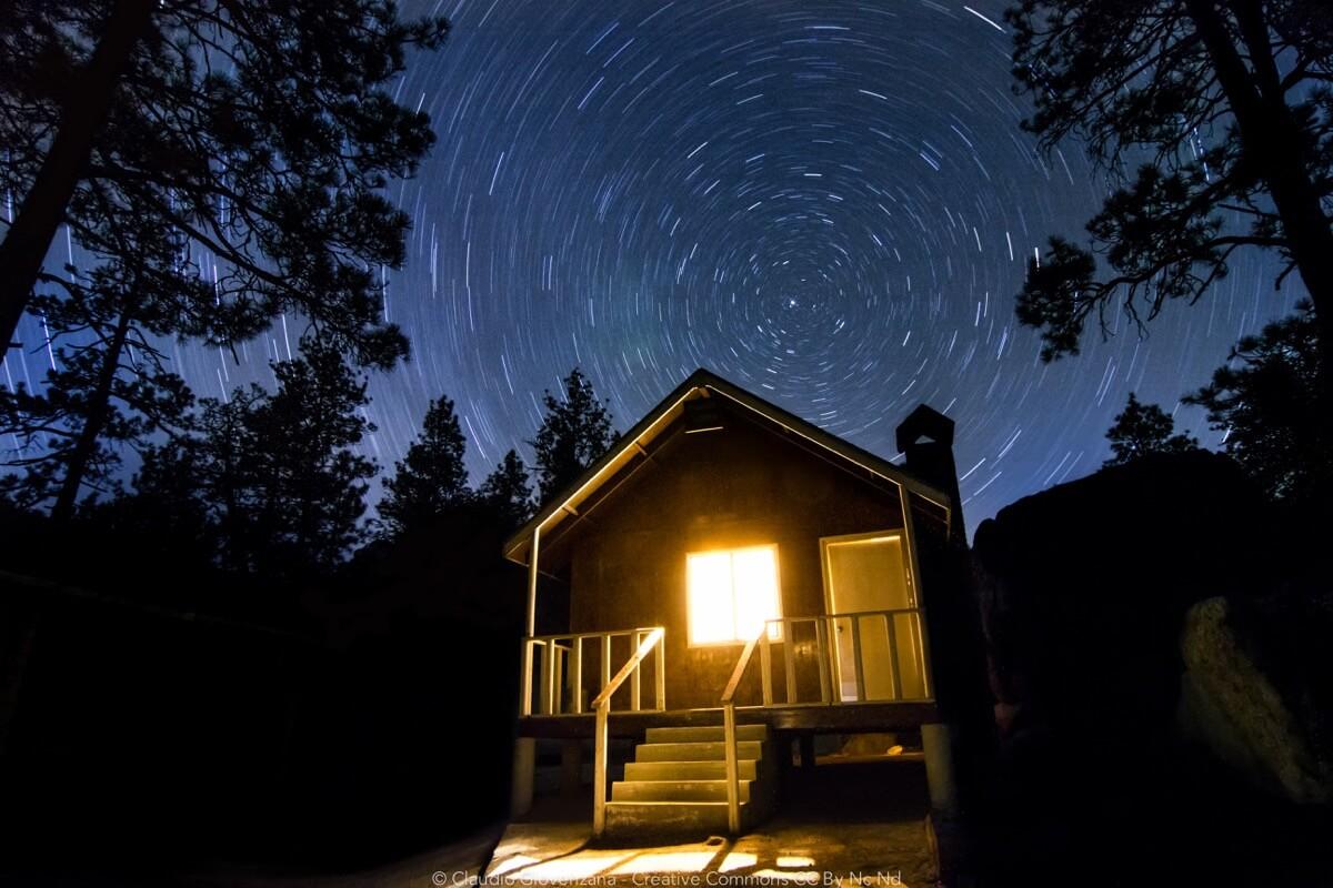 Il bosco una capanna e una lunga esposizione notturna per vedere le stelle che si muovo nel cielo