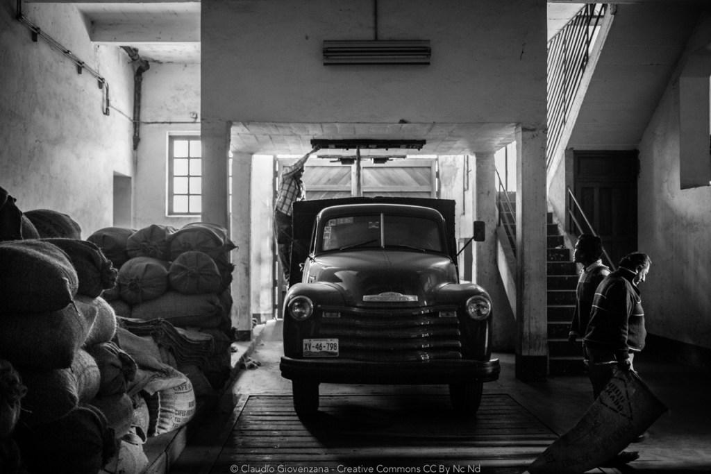 una fabbrica che processa caffe in Messico con un vecchio furgone sacchi di iuta e varie persone