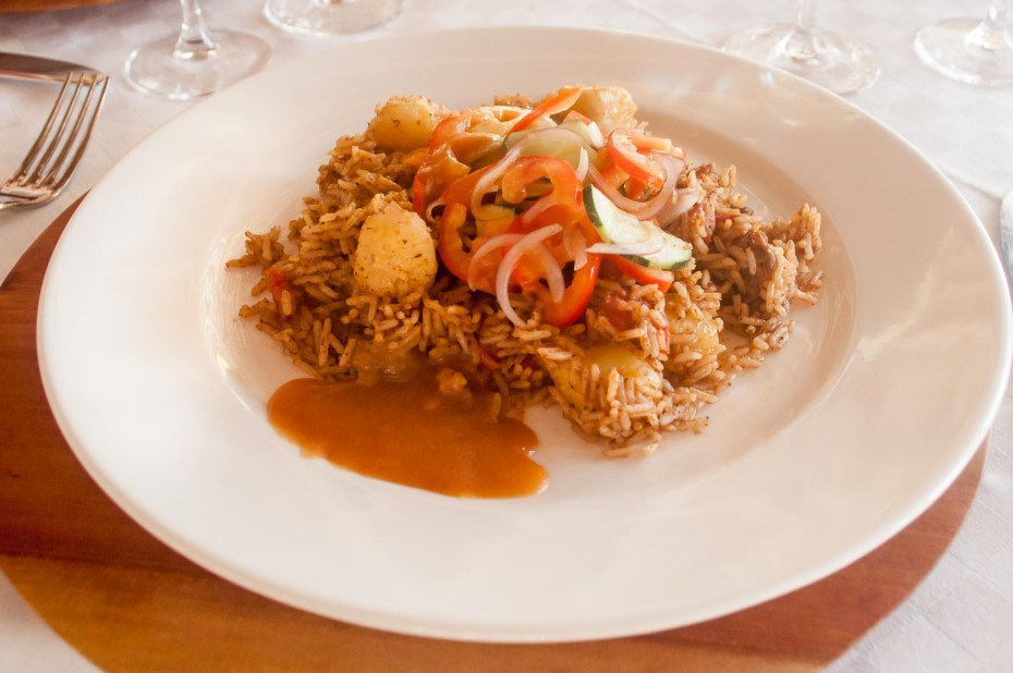 Pilau Swahili dish with rice mixed with spices, tomatoes, potatoes and beef meat, served with kachumbari salad