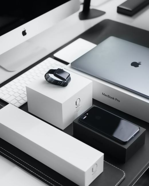 space black case Apple Watch, silver MacBook Pro, jet black iPhone 7 Plus, and silver iMac with corresponding boxes