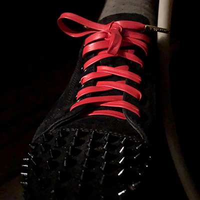 Front view of louboutin sneakers with leather red shoelaces