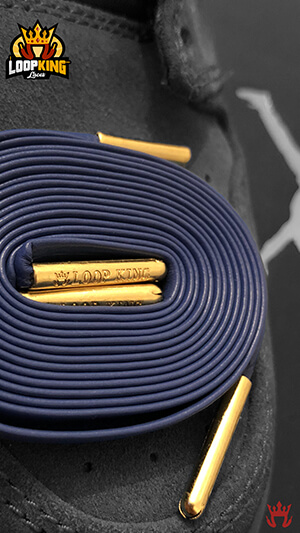 Close up of royal blue shoelaces with gold tips
