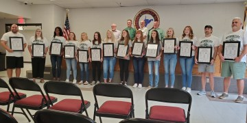 """The Wyoming East girls basketball team poses after being honored for the Class AA championship run.  (Pictured from left to right coaches Tim Leather and Angie Boninsegna, players Daisha Summers,  Savannah Smoot, Skylar Davidson, Abby Russell, Hannah Blankenship, Colleen Lookabill, Sarah Saunders, Laken Toler, Charleigh Price, Emma Blankenship, and coaches Ryan Davidson and Max Boyce. Second row: BOE members Allan Stiltner, Mike Pritchard, Morgan """"Mike"""" Davis and Richard Walker.  Photo submitted by Sonny Boninsegna)"""