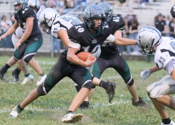 (Brad Davis/For LootPress) Wyoming East's Chandler Johnson cuts between Westside's Colton Moore, left, and Andy Elkins to pick up a chunk of yards Friday night in New Richmond.