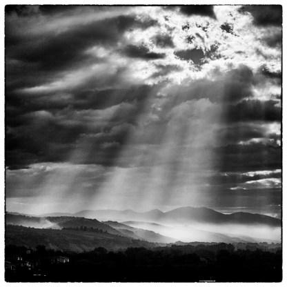 Luce che filtra fra le nuvole ed illumina la campagna nebbiosa