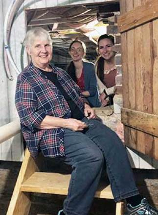 Above, from left, Heritage Center Archives and Museum Director Eleanor Craig, Curator Susanna Pyatt and Archivist Ayla Toussaint explore the crawl space beneath the Heritage Center.