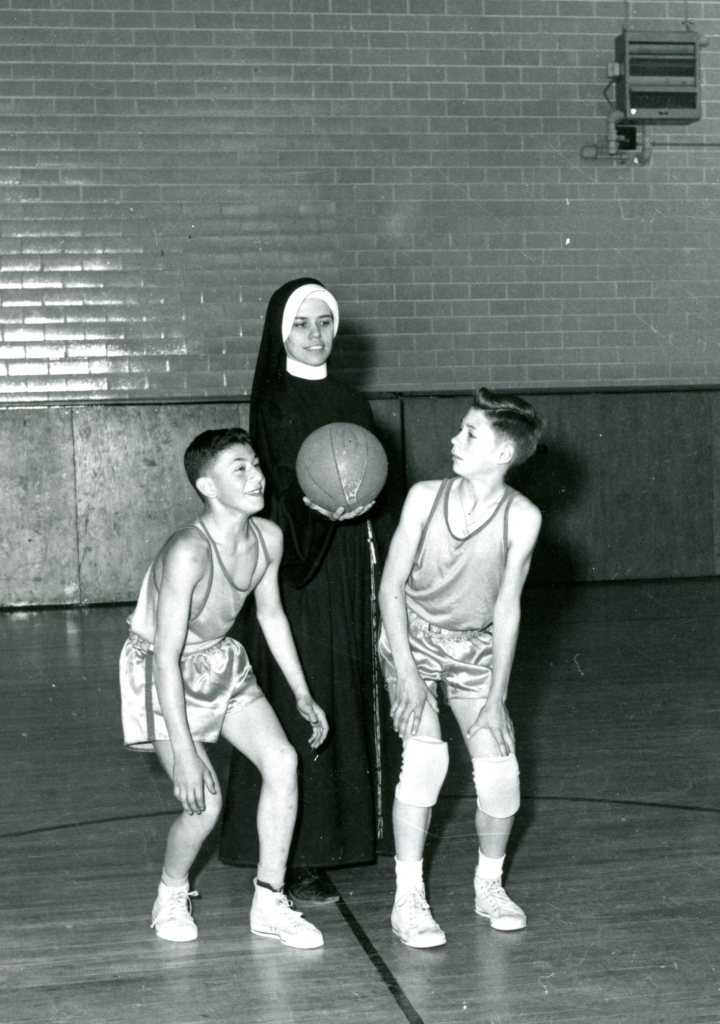 Two boys in basketball uniforms prepare to jump for a ball when the Sister tosses it