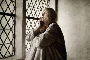 Old woman in ancient asylum suffers alone, because psychiatric disorders were misunderstood, showing the stigmatizing term: mentally ill is no longer relevant.