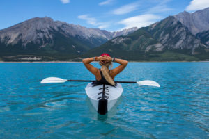 Woman in a kayak in a beautiful lake sits back and enjoys the view after IV ketamine relieved her treatment-resistant depression.