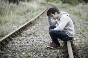 Can inflammation cause suicide? Young man sits on train tracks.