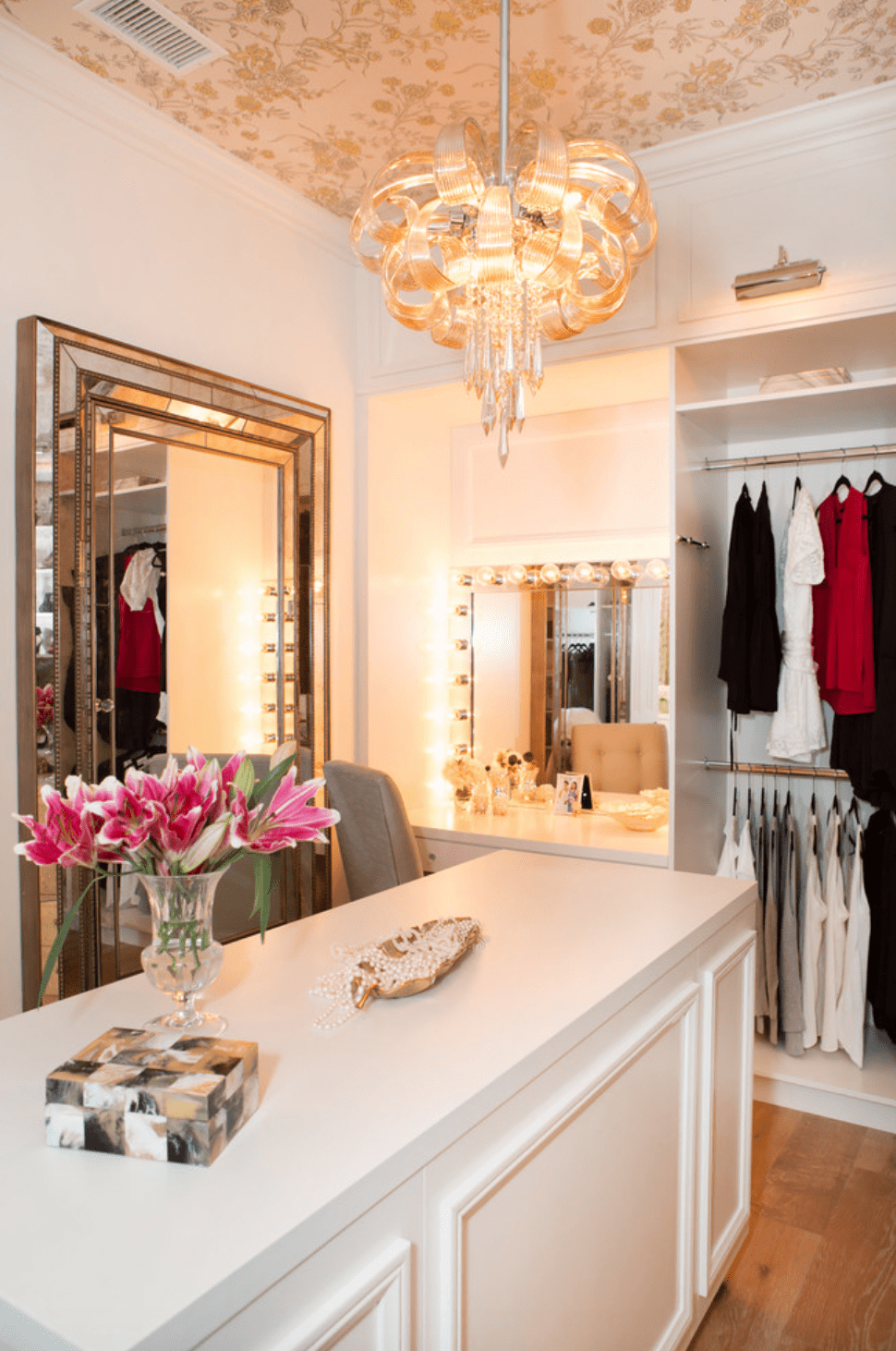 Wallpapered ceiling and white cabinets in custom dream closet