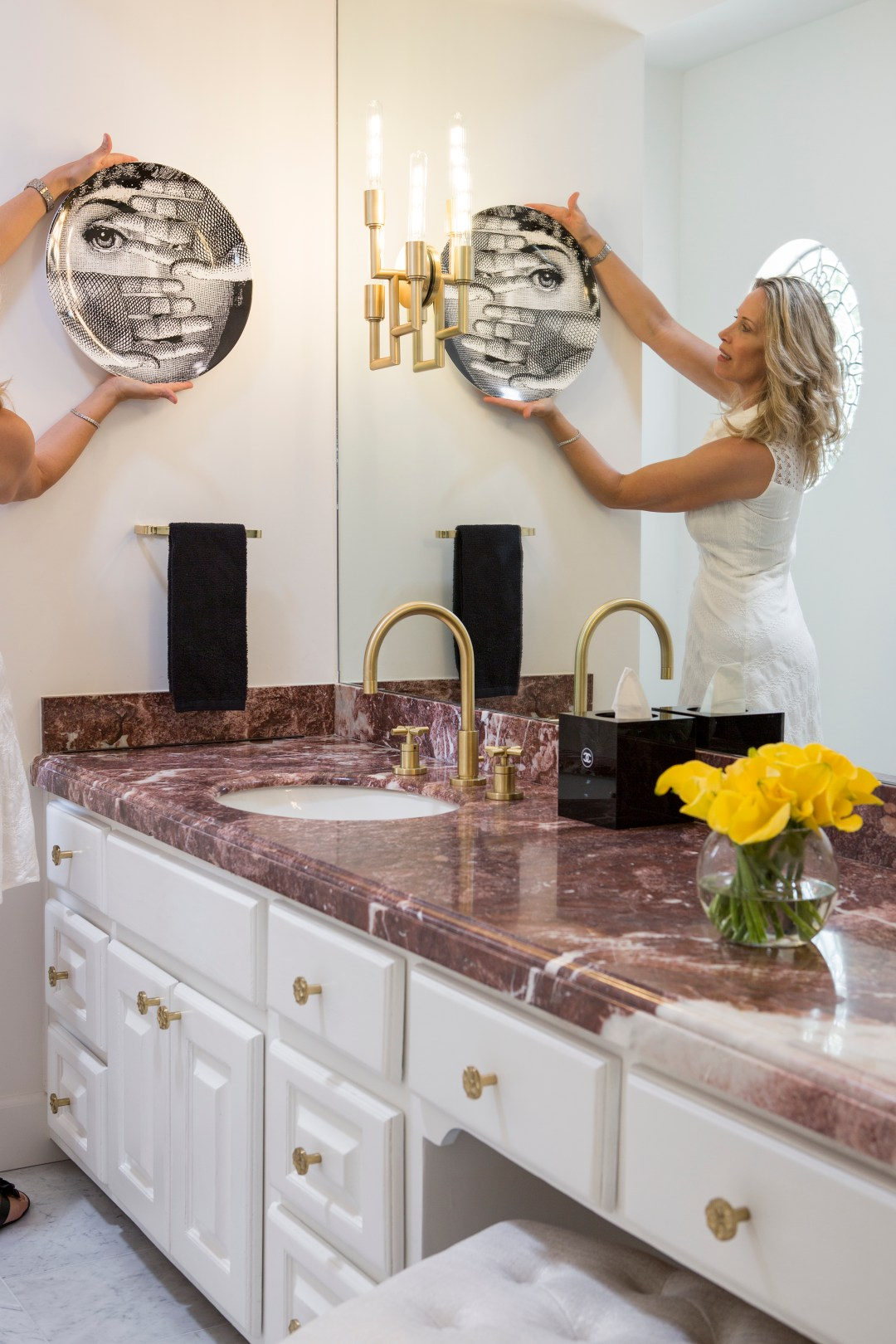 Lori Dennis hangs fornasetti decorative plate on bel air road bathroom wall next to lamps plus brass sconce