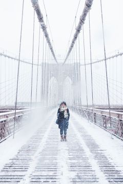 Woman crossing a bridge, snow blowing everywhere