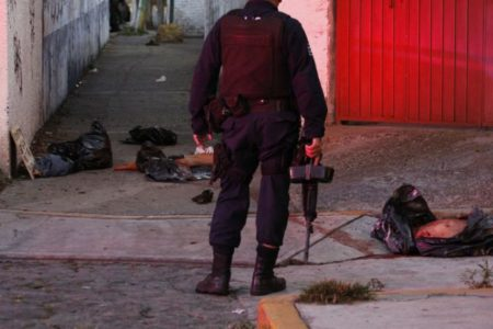 A police officer next to various body parts in black plastic bags in Cuernavaca, Mexico, in 2012.Margarito Perez Retana/Reuters