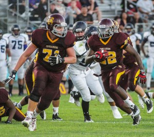 PHOTO BY MIKE ZOETEWEY   Valley Christian sophomore right guard Eric Schoonover provides ample room for senior running back Jonathan Nicholson to pick up some yards in last Friday night's season-opening 50-6 win over Duarte. Nicholson rushed for 146 yards on 16 carries and scored four touchdowns.