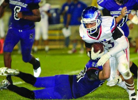 John Glenn junior running back Carlos Pulido tries to gain some yardage but is dragged down by Norwalk junior safety Andrew Navarro in last Friday night's city rivalry game. Norwalk beat Glenn 46-14, the 14th straight win over the Eagles. PHOTO BY ARMANDO VARGAS, Contributing photographer