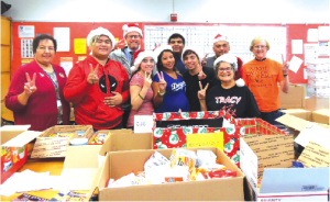 """TRACY HELPING TROOPS OVERSEAS: Tracy Students and staff in front of the goodies collected for the troops overseas. Principal Jeff Green, third from left, who's son was stationed in Afghanistan as a helicopter pilot years ago once told his dad """"the boxes were a god-send."""" He joked they could sell a can of Chef-Boy-R Dee for $20 if they wanted. Money donations are also accepted, each box sent cost $17.90. The last possible date to contribute to the gift boxes is December 20th. Donations should go to Tracy ASB or contact 562.926.5566 extension 22201. Photo by Tammye McDuff."""