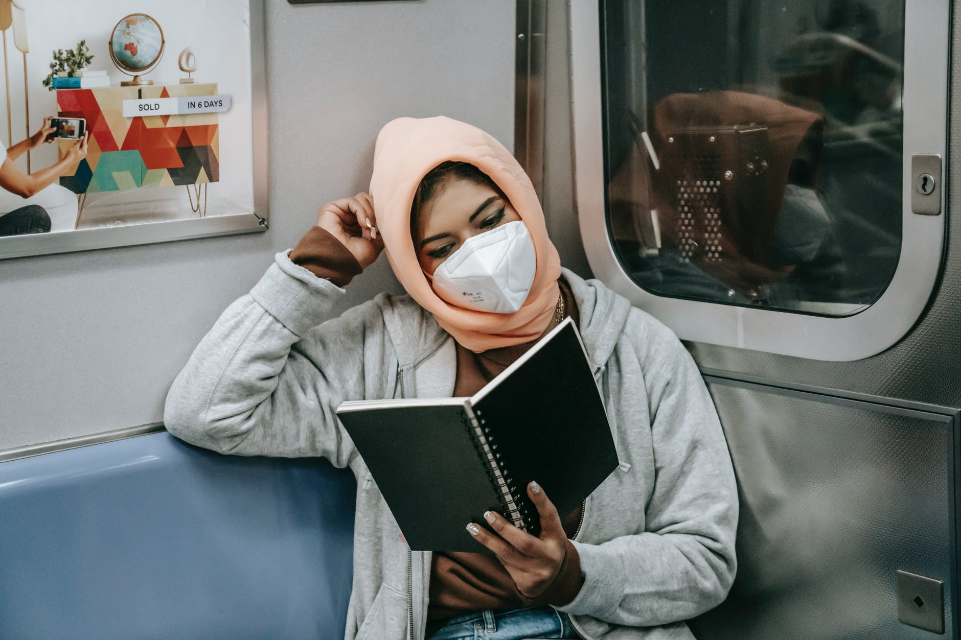 unrecognizable ethnic lady sitting and reading in train in mask