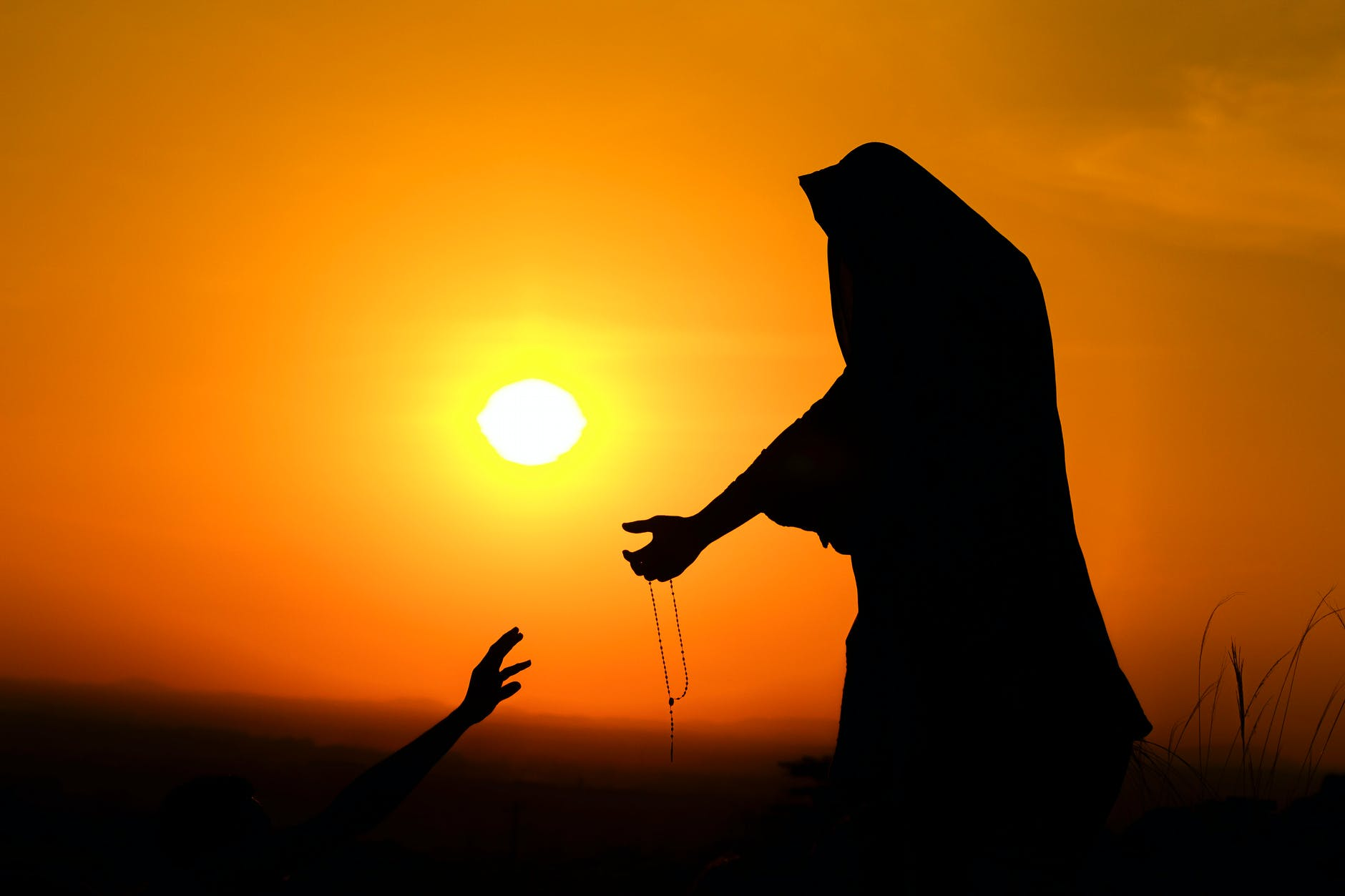 silhouette of woman outstretching hand to help man at sundown