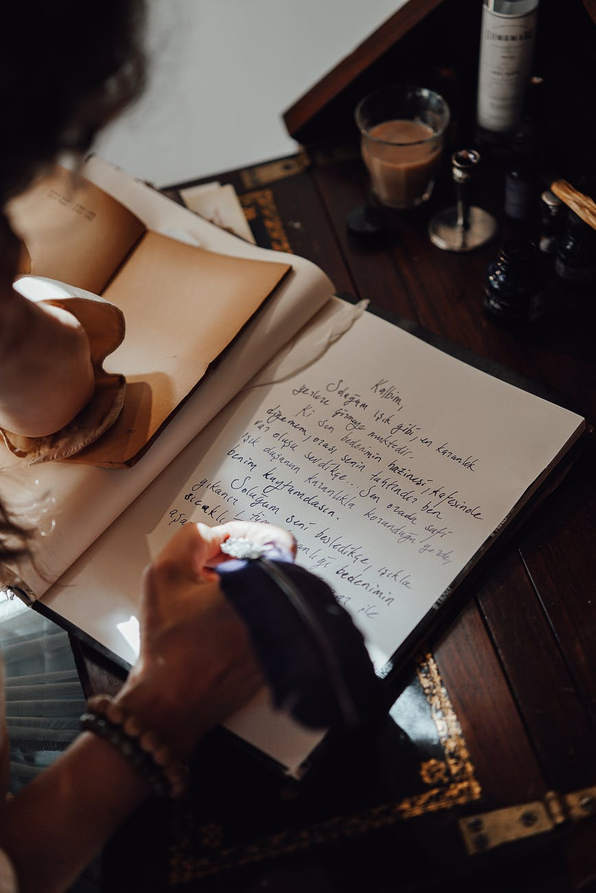 crop author writing novel in notebook at aged table