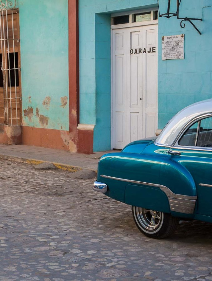 A street in Trinidad Cuba with an old blue american car on right and a person sitting in an aqua doorway on left