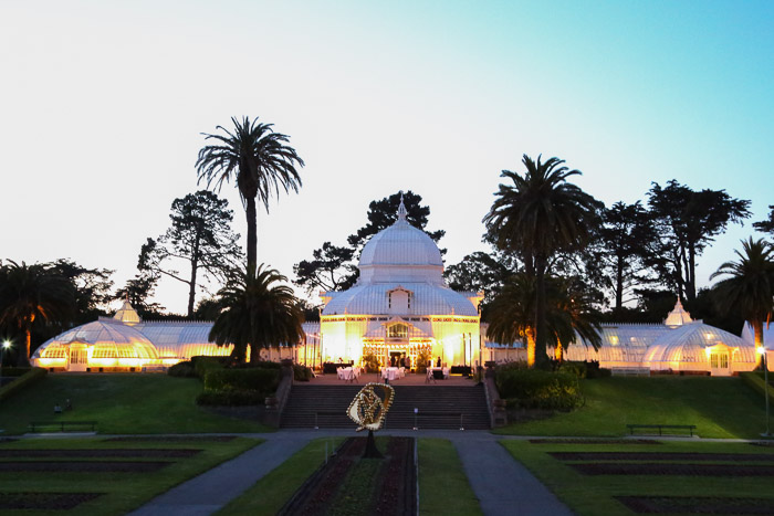 Conservatory of Flowers building illuminated in early evening in San Francisco | Lost Not Found | SF Travel Guide
