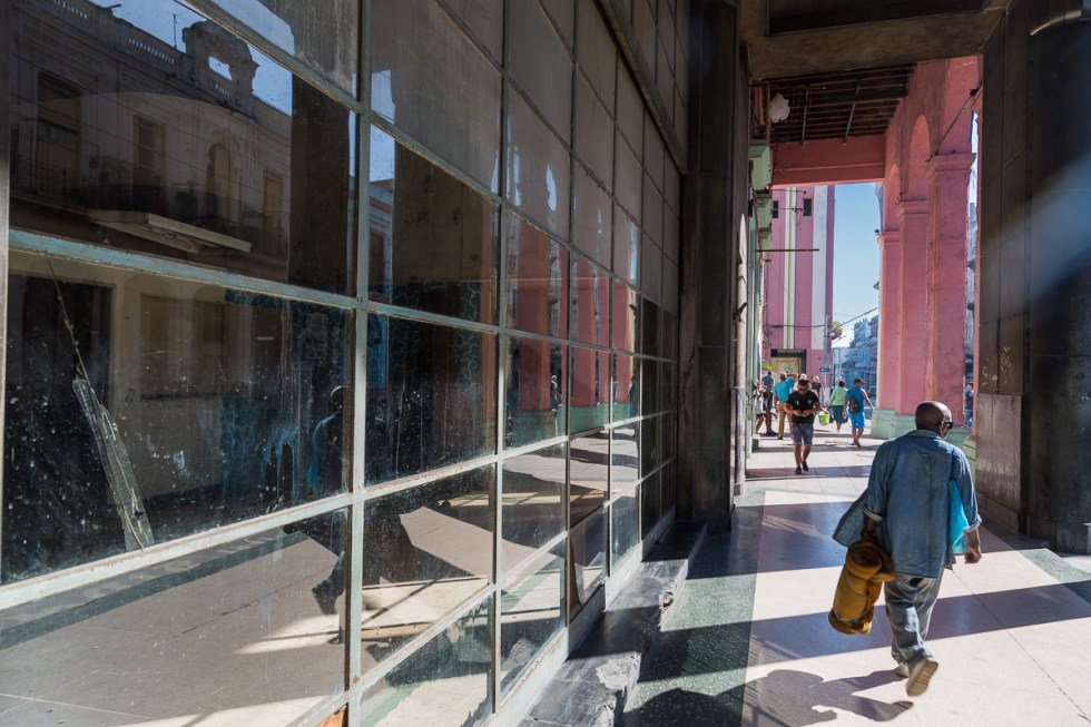 A man walking along a busy street in Havana and reflections of buildings in the glass | LOST NOT FOUND| La Habana | Cuba | Havana | Street Photography