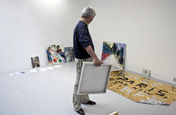 Het verschuiven begint, Kees Koomen loopt met schilderijen