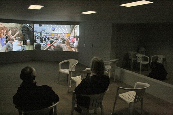 Aernout Mik - Tongues and Assistants - Tweekanaals videoinstallatie zonder geluid met live installatie