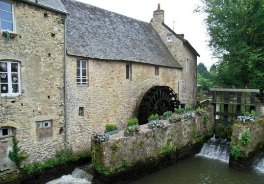 Industrial Medieval Buildings | A water mill in Normandy that utilizes a gated weir to control water flow.