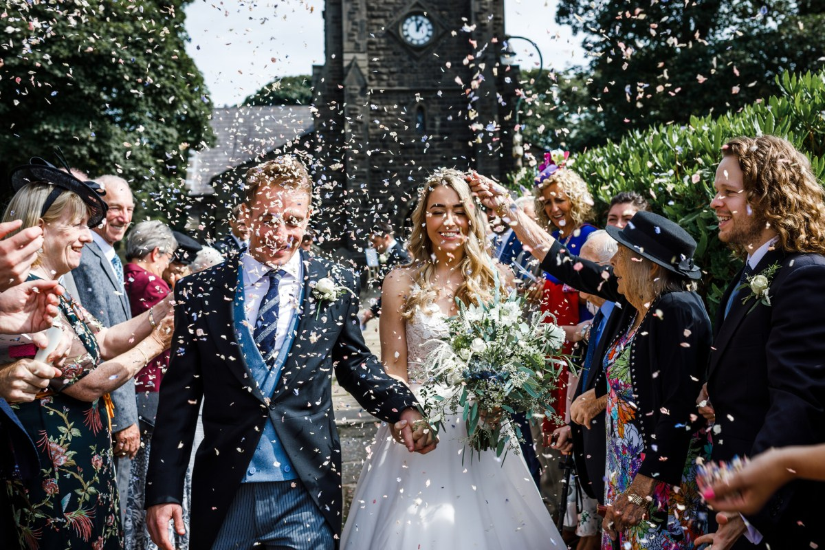 Bride and groom walking through lots of confetti in Lancashire