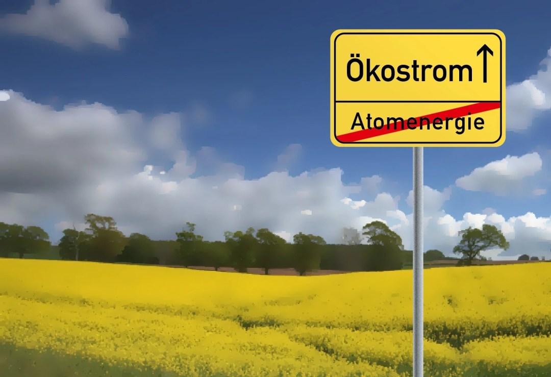 Ein deutsches Ortsschild: Ökostrom, darunter durchgestrichen Atomenergie, dahinter ein Rapsfeld und einige Bäume vor leicht bewölktem Himmel (cc) Pixabay