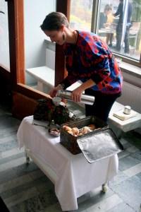 Louise Blad står framför ett bord med en vit duk, en plåtlåda med mera. Louise håller upp något i en kopp från en grå termos. Foto: Elin Magnusson.