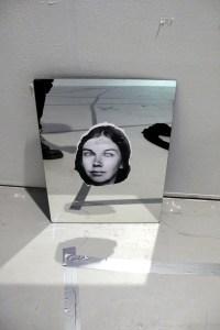 Bild på en spegel som står i ett vitt rum. På spegeln finns en utklippt bild av en persons ansikte. Spegeln och bilden reflekterar ljus i golvet.