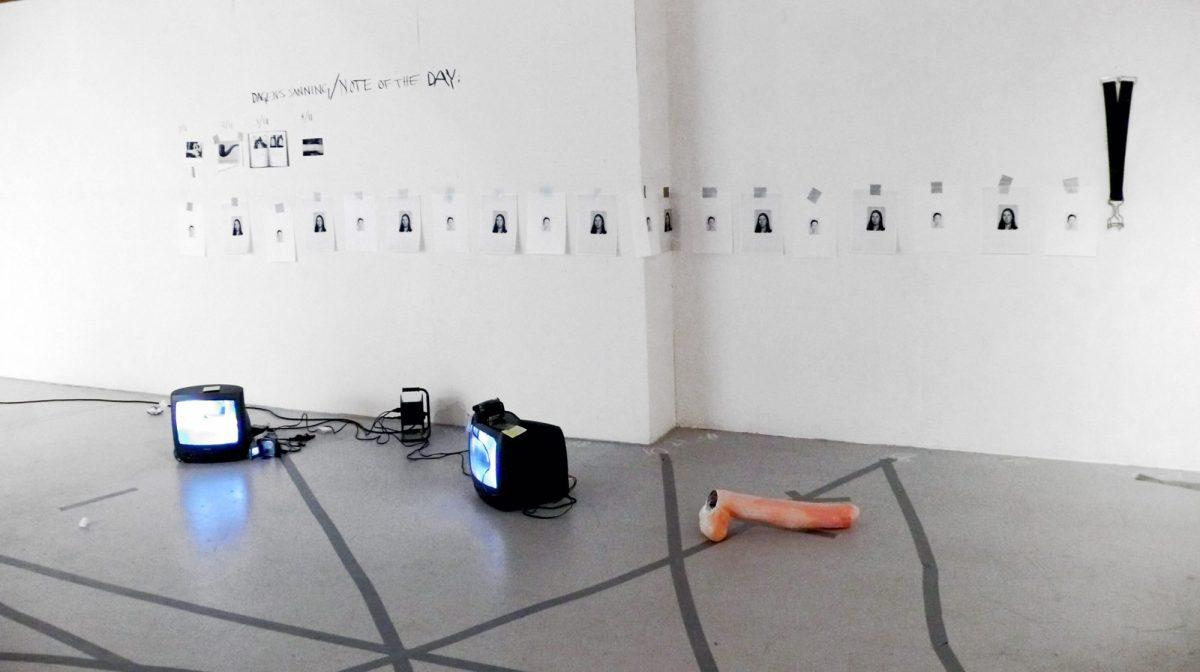 """Äga rum. Bild på ett vitt rum med grått golv. Golvet har mörkgråa streck över sig. På golvet står två TV-apparater. På väggen hänger många A4-ark med en person på. Det står också """"Dagens sanning/note of the day"""" på väggen."""