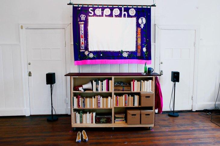 """Bild på installationsvyn på Italienska palatset, 2016. En projektorduk som är i lila material med en vit fyrkant för själva duken. Det står """"Sappho"""" och den har flera kvinnotecken på dig. Under den står en bokhylla."""