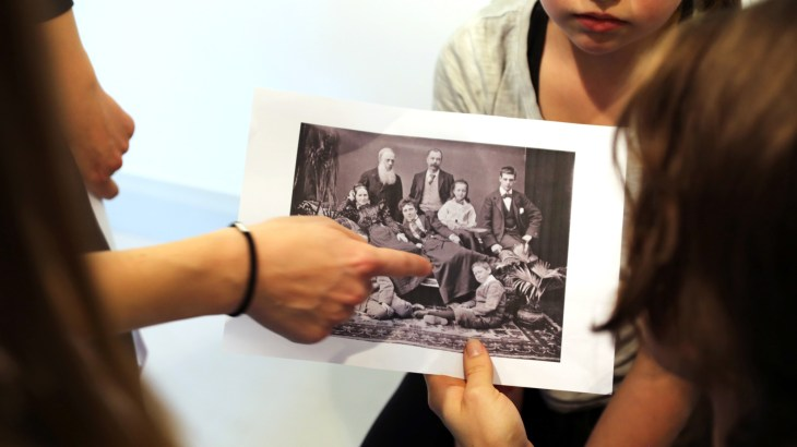 Tre-fyra personer tittar och pekar på ett gammalt fotografi där åtta personer är uppställda för ett gruppfoto. Foto: Calle Holck