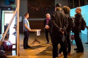 Bild på Louise Blad som står framför en grupp människor. De står framför en tillfällig vägg. Foto: Björn Bengtsson