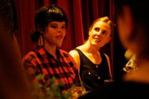 Bild på två personer på middagsbjudning. Bakom dem hänger ett rött sammetsdraperi. Foto: Eva Mag