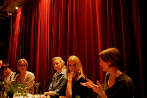 Bild på fem personer på middagsbjudning. Bakom dem hänger ett rött sammetsdraperi. Foto: Eva Mag