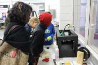 Visitors observe a 3D printer in action in the Rapid Prototyping Center.