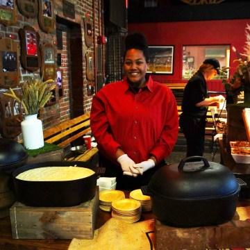 A preparer serves cheddar corn grits (left) and oxtail soup (black cast iron pot).