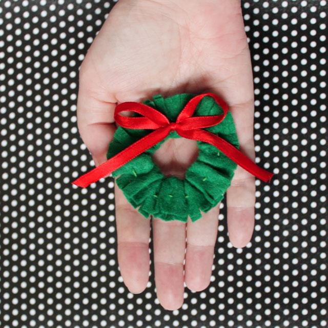 holding-handmade-felt-and-ribbon-wreath-christmas-gift-topper