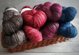 Yarn skeins in blue red silver in basket