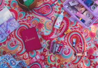 Spread of crochet accessories including hand cream hooks caddy notebook stitch markers