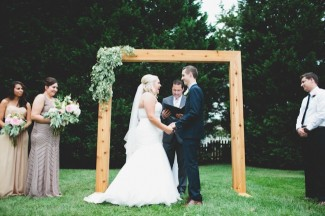 bride and groom standing at square wood altar during ourdoor ceremony