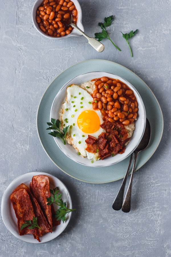 savory oatmeal topped with baked beans, egg and bacon
